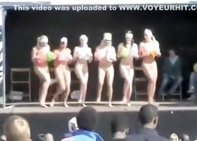 Naked ladies dance on stage with balloons