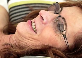 Granny with glasses smiles as the partner explores her inner depths